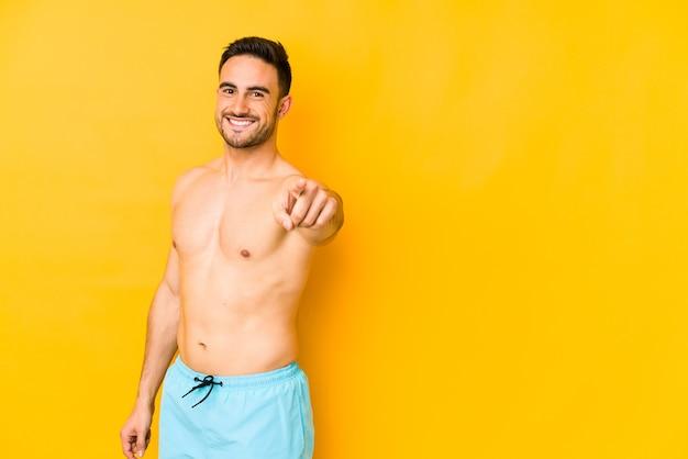 Junger kaukasischer mann mit badeanzug lokalisiert auf gelbem hintergrund junger kaukasischer mann mit dem zeigen nach vorne mit den fingern.