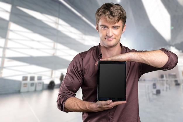 Junger kaukasischer mann mit beweglichem pc in seinen händen