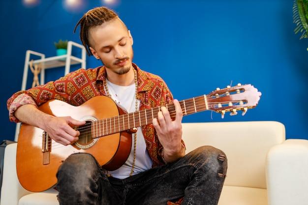 Junger kaukasischer mann mit dreadlocks, die auf sofa sitzen und akustische gitarre spielen