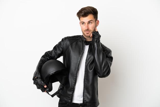 Junger kaukasischer mann mit einem motorradhelm, der auf weißem hintergrund isoliert ist und beim nachschlagen eine idee denkt