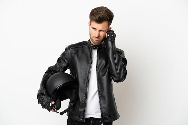 Junger kaukasischer mann mit einem motorradhelm isoliert auf weißem hintergrund frustriert und bedeckt die ohren