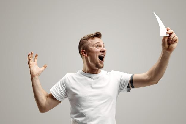 Junger kaukasischer mann mit einem überraschten glücklichen ausdruck gewann eine wette auf grauem studiohintergrund. menschliche gesichtsgefühle und wettkonzept