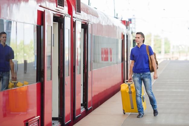 Junger kaukasischer mann mit gepäck an der station, die mit dem zug reist