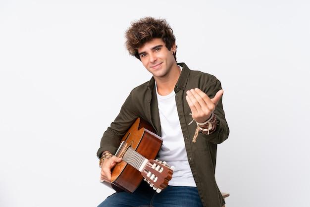 Junger kaukasischer mann mit gitarre über der lokalisierten weißen wand, die einlädt zu kommen