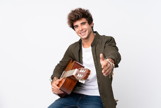 Junger kaukasischer mann mit gitarre über isoliertem weißem wandhandschütteln nach vielem