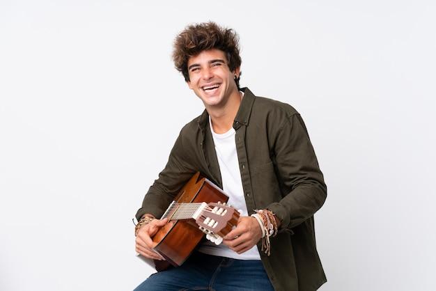 Junger kaukasischer mann mit gitarre über isoliertem weißem wandlachen