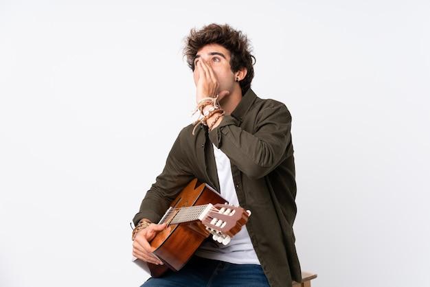 Junger kaukasischer mann mit gitarre über isolierter weißer wand, die mit offenem mund schreit