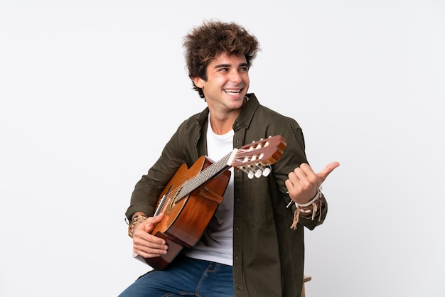 Junger kaukasischer mann mit gitarre über lokalisierter weißer wand finger auf die seite zeigend