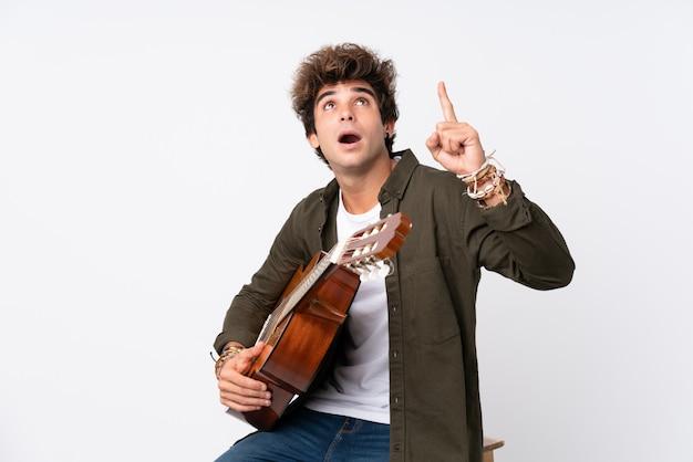 Junger kaukasischer mann mit gitarre über lokalisierter weißer wand zeigend mit dem zeigefinger eine großartige idee