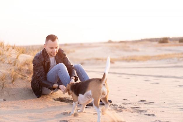 Junger kaukasischer mann mit hund beagle sitzt am sandstrand