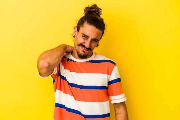 Junger kaukasischer mann mit langen haaren auf gelbem hintergrund mit schulterschmerzen.