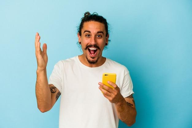 Junger kaukasischer mann mit langen haaren, der ein mobiltelefon isoliert auf blauem hintergrund hält und eine angenehme überraschung empfängt, aufgeregt und die hände hebt