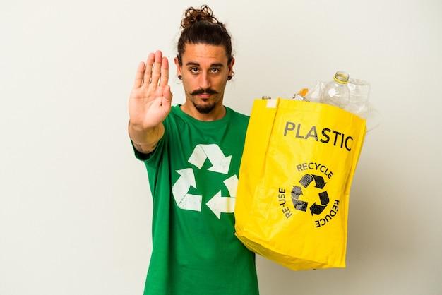 Junger kaukasischer mann mit langen haaren, die kunststoff auf weißem hintergrund recyceln, der mit ausgestreckter hand steht und stoppschild zeigt und sie verhindert.