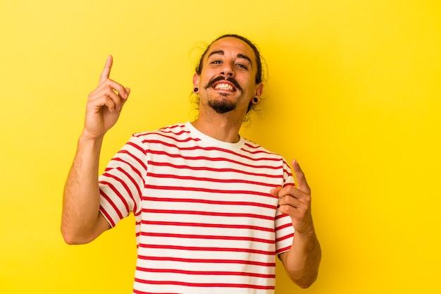 Junger kaukasischer mann mit langen haaren isoliert auf gelbem hintergrund tanzen und spaß haben.