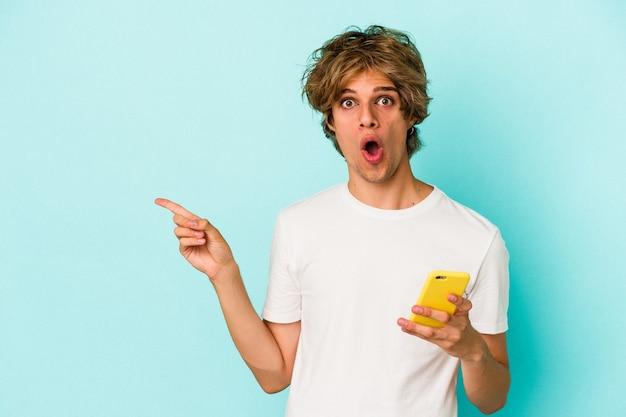 Junger kaukasischer mann mit make-up, der das mobiltelefon isoliert auf blauem hintergrund hält und zur seite zeigt