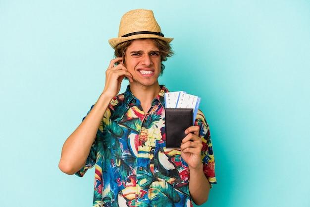 Junger kaukasischer mann mit make-up, der den pass auf blauem hintergrund isoliert hält und die ohren mit den händen bedeckt.