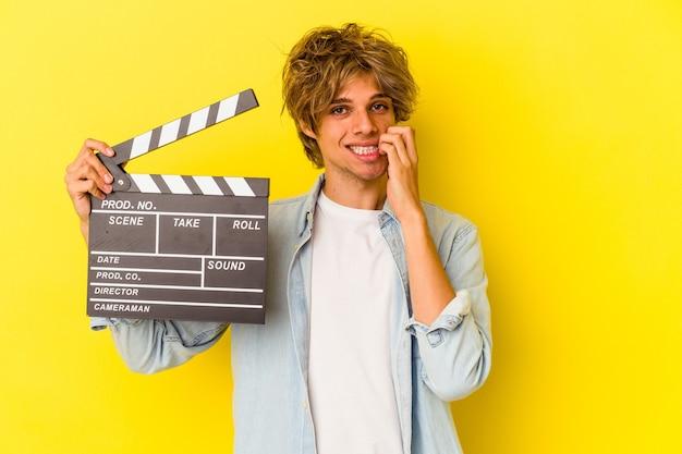 Junger kaukasischer mann mit make-up, der die klappe einzeln auf gelbem hintergrund hält und fingernägel beißt, nervös und sehr ängstlich.