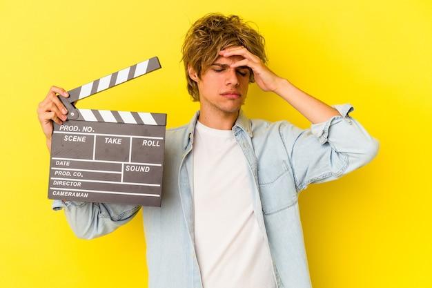 Junger kaukasischer mann mit make-up, der die klappe einzeln auf gelbem hintergrund hält und schockiert ist, hat sich an ein wichtiges treffen erinnert.