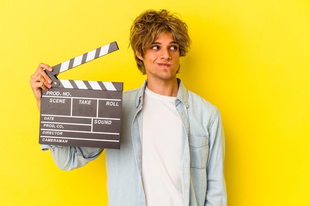 Junger kaukasischer mann mit make-up, der die klappe einzeln auf gelbem hintergrund hält, verwirrt, fühlt sich zweifelhaft und unsicher.