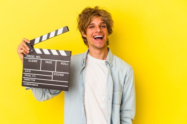 Junger kaukasischer mann mit make-up, der die klappe isoliert auf gelbem hintergrund hält, glücklich, lächelnd und fröhlich.