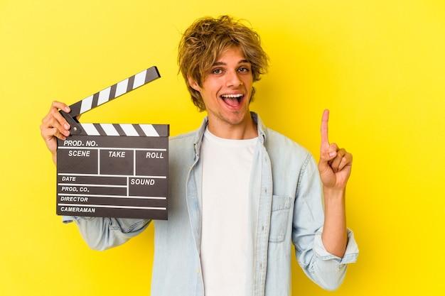 Junger kaukasischer mann mit make-up, der die klappe isoliert auf gelbem hintergrund hält und die nummer eins mit dem finger zeigt.