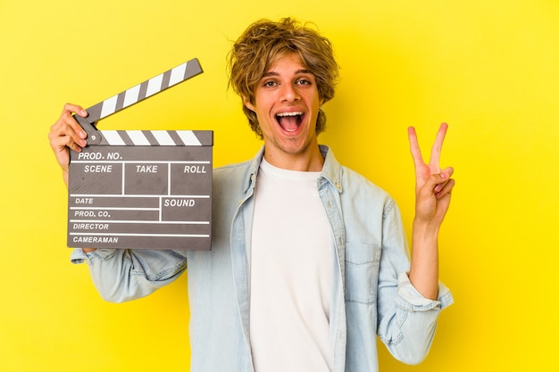 Junger kaukasischer mann mit make-up, der die klappe isoliert auf gelbem hintergrund hält und die nummer zwei mit den fingern zeigt.