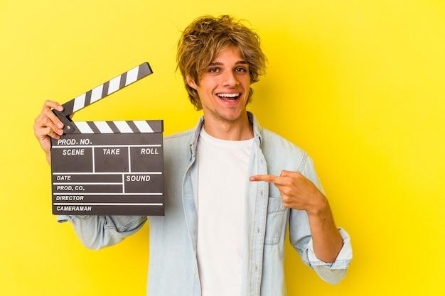 Junger kaukasischer mann mit make-up, der die klappe isoliert auf gelbem hintergrund hält und lächelt und beiseite zeigt, etwas an der leerstelle zeigend.