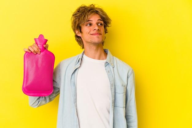 Junger kaukasischer mann mit make-up, der eine heiße tüte wasser isoliert auf gelbem hintergrund hält und davon träumt, ziele und zwecke zu erreichen