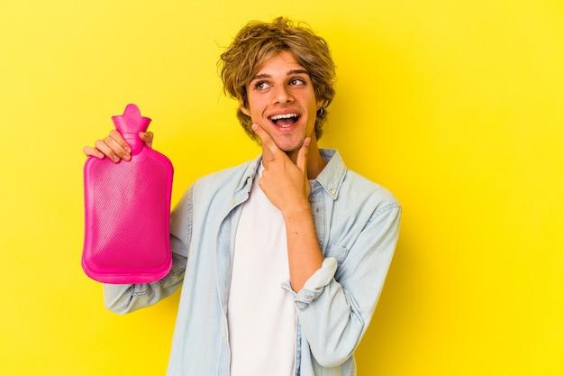 Junger kaukasischer mann mit make-up, der eine heiße tüte wasser isoliert auf gelbem hintergrund hält und seitlich mit zweifelhaftem und skeptischem ausdruck schaut.