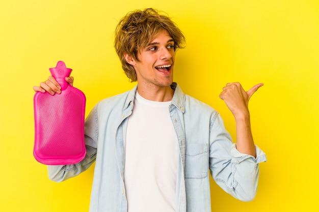 Junger kaukasischer mann mit make-up, der eine heiße tüte wasser isoliert auf gelbem hintergrund hält, zeigt mit dem daumen weg, lacht und sorglos.
