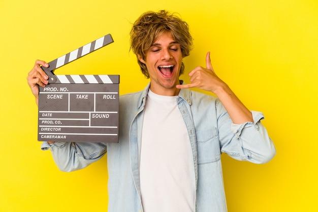 Junger kaukasischer mann mit make-up, der eine klappe isoliert auf gelbem hintergrund hält und eine handy-anrufgeste mit den fingern zeigt.