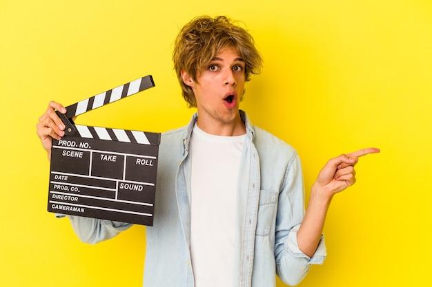 Junger kaukasischer mann mit make-up, der eine klappe isoliert auf gelbem hintergrund hält und zur seite zeigt