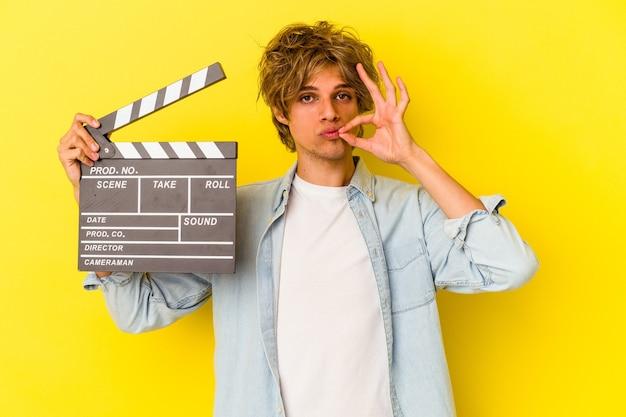 Junger kaukasischer mann mit make-up, der eine klappe isoliert auf gelbem hintergrund mit den fingern auf den lippen hält, die ein geheimnis halten.