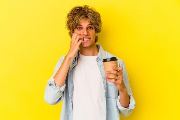 Junger kaukasischer mann mit make-up, der einen kaffee zum mitnehmen hält, isoliert auf gelbem hintergrund, der fingernägel beißt, nervös und sehr ängstlich.
