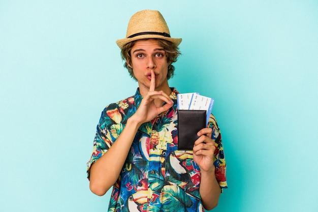 Junger kaukasischer mann mit make-up, der einen pass auf blauem hintergrund hält, der ein geheimnis hält oder um stille bittet.