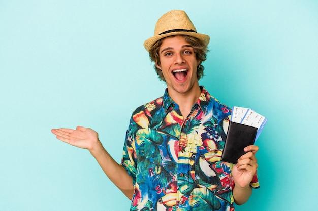 Junger kaukasischer mann mit make-up, der einen reisepass einzeln auf blauem hintergrund hält, der einen kopienraum auf einer handfläche zeigt und eine andere hand an der taille hält.