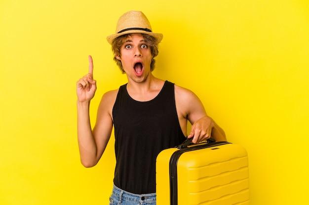 Junger kaukasischer mann mit make-up, der isoliert auf gelbem hintergrund mit einer idee, einem inspirationskonzept reisen wird.