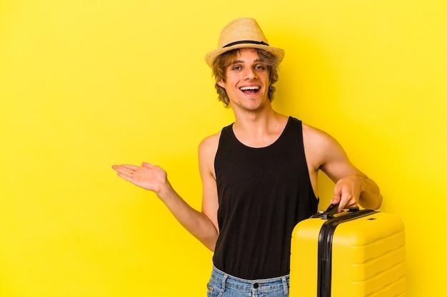 Junger kaukasischer mann mit make-up, der isoliert auf gelbem hintergrund reisen wird, der einen kopienraum auf einer handfläche zeigt und eine andere hand an der taille hält.