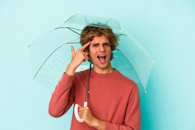 Junger kaukasischer mann mit make-up, der regenschirm isoliert auf blauem hintergrund hält und eine enttäuschungsgeste mit dem zeigefinger zeigt.