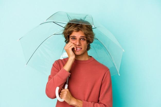 Junger kaukasischer mann mit make-up, der regenschirm isoliert auf blauem hintergrund hält und fingernägel beißt, nervös und sehr ängstlich.