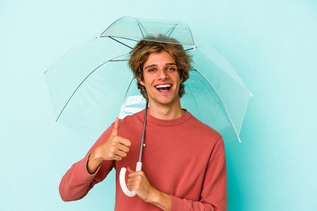 Junger kaukasischer mann mit make-up, der regenschirm isoliert auf blauem hintergrund hält und lächelt und daumen hochhebt