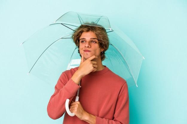 Junger kaukasischer mann mit make-up, der regenschirm isoliert auf blauem hintergrund hält und seitlich mit zweifelhaftem und skeptischem ausdruck schaut.