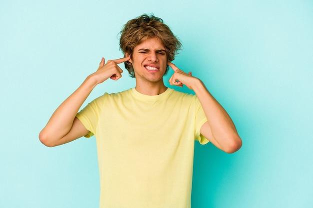 Junger kaukasischer mann mit make-up einzeln auf blauem hintergrund, der die ohren mit den fingern bedeckt, gestresst und verzweifelt durch eine laute umgebung.
