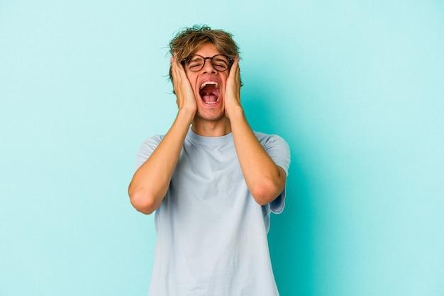 Junger kaukasischer mann mit make-up isoliert auf blauem hintergrund weint, unglücklich mit etwas, qual und verwirrung konzept.