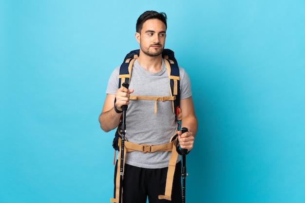 Junger kaukasischer mann mit rucksack und trekkingstöcken lokalisiert auf blau mit zweifeln beim betrachten der seite
