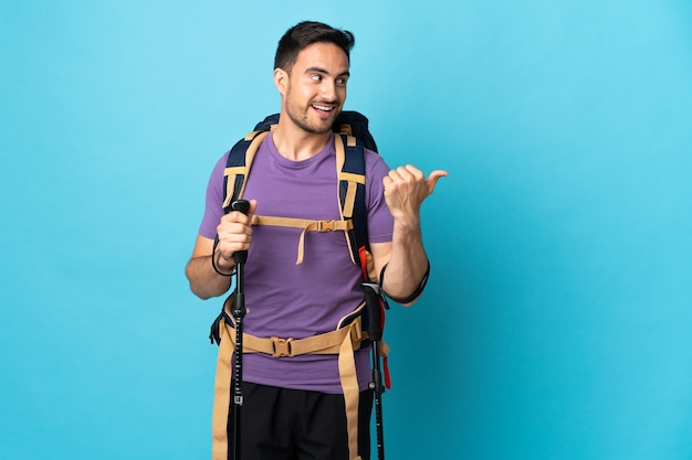 Junger kaukasischer mann mit rucksack und wanderstöcken lokalisiert auf blauer wand, die zur seite zeigt, um ein produkt zu präsentieren