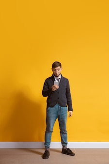 Junger kaukasischer mann mit smartphone ganzkörper-längenporträt über gelb