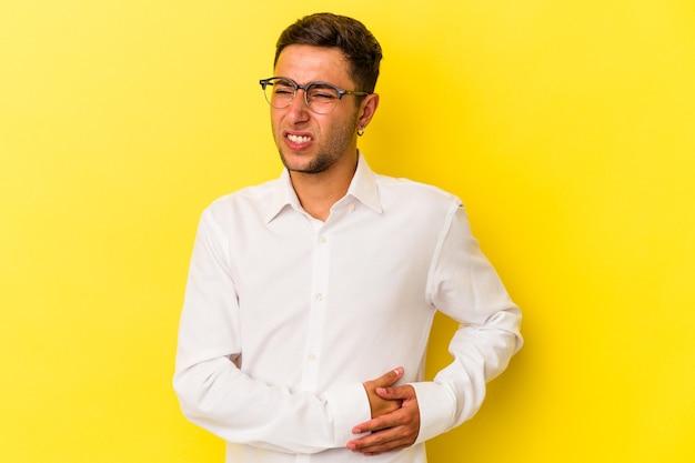 Junger kaukasischer mann mit tätowierungen auf gelbem hintergrund mit leberschmerzen, bauchschmerzen.