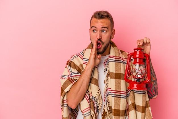 Junger kaukasischer mann mit tätowierungen, der eine vintage-laterne isoliert auf rosa hintergrund hält, sagt eine geheime heiße bremsnachricht und schaut beiseite