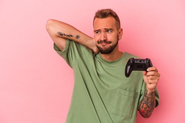 Junger kaukasischer mann mit tätowierungen, der einen gamecontroller einzeln auf rosafarbenem hintergrund hält, der den hinterkopf berührt, denkt und eine wahl trifft.
